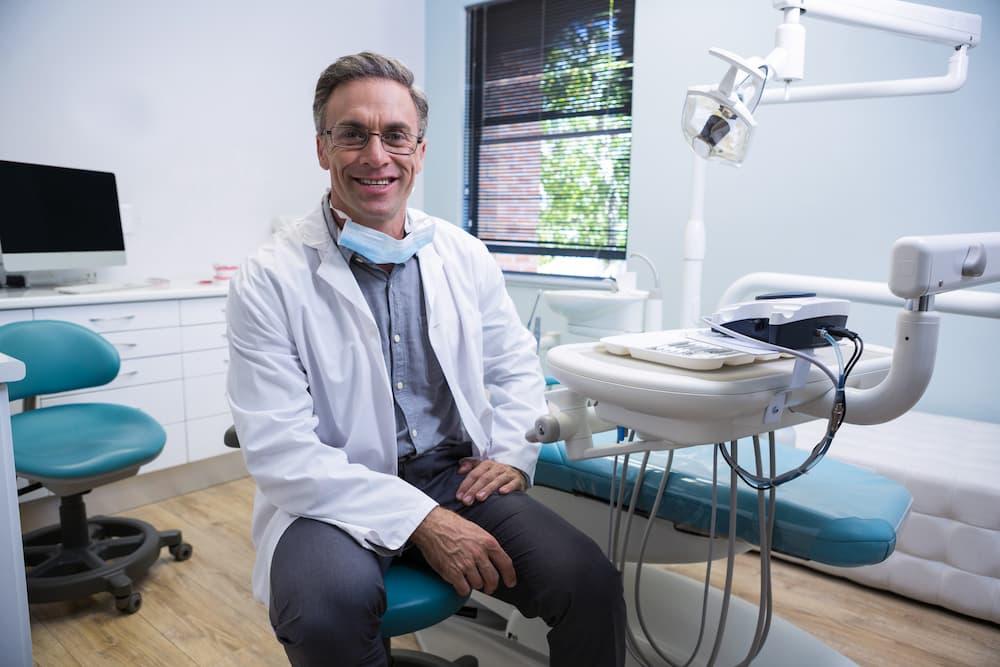 portrait-of-smiling-dentist-sitting-on-chair-76JSMLK (1)